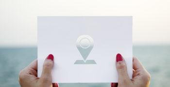 Kobiece-dlonie-trzymajace-kartke-z-symbolem-lokalizacji